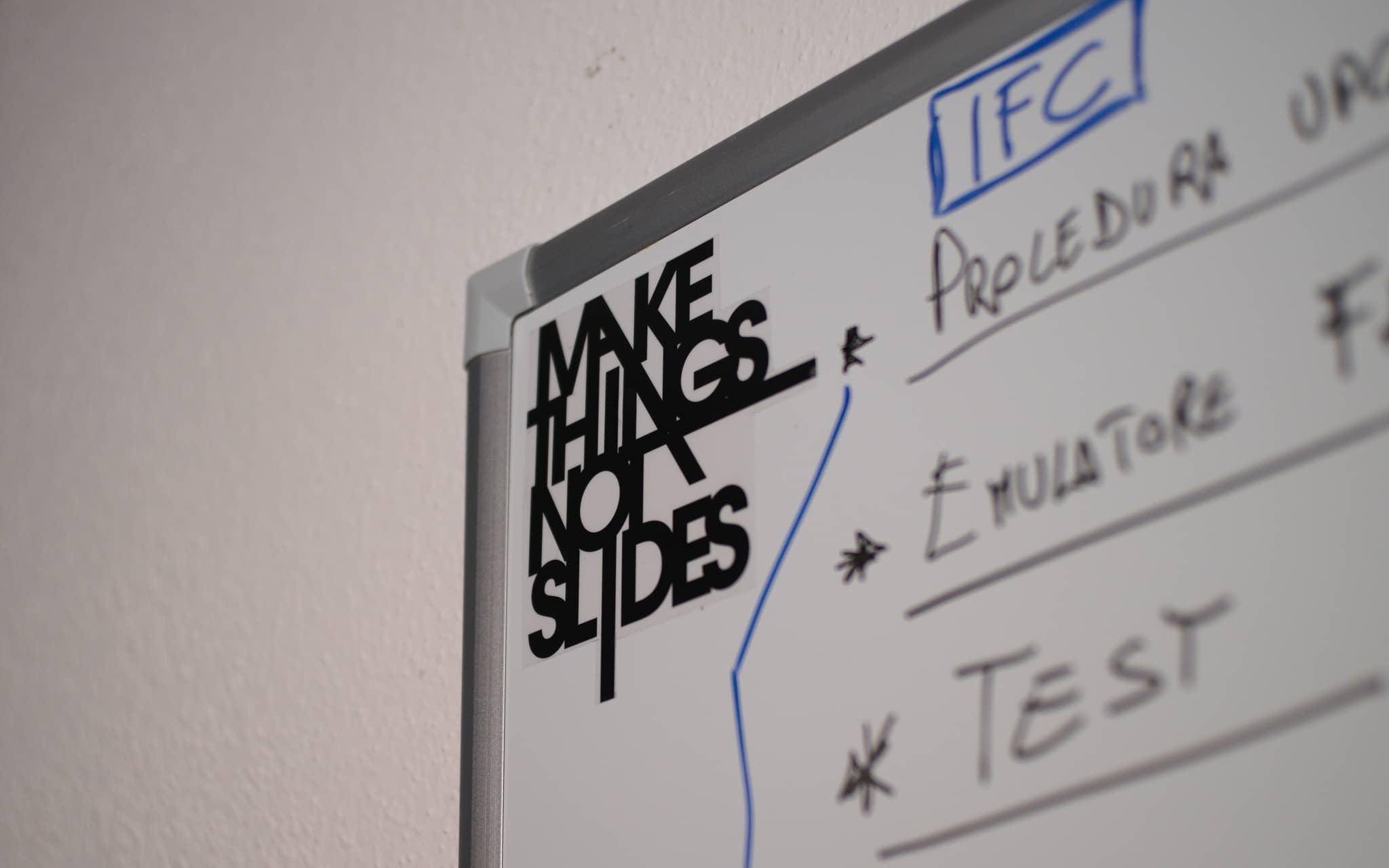 Lavagna con adesivo 'Make things, not slides'